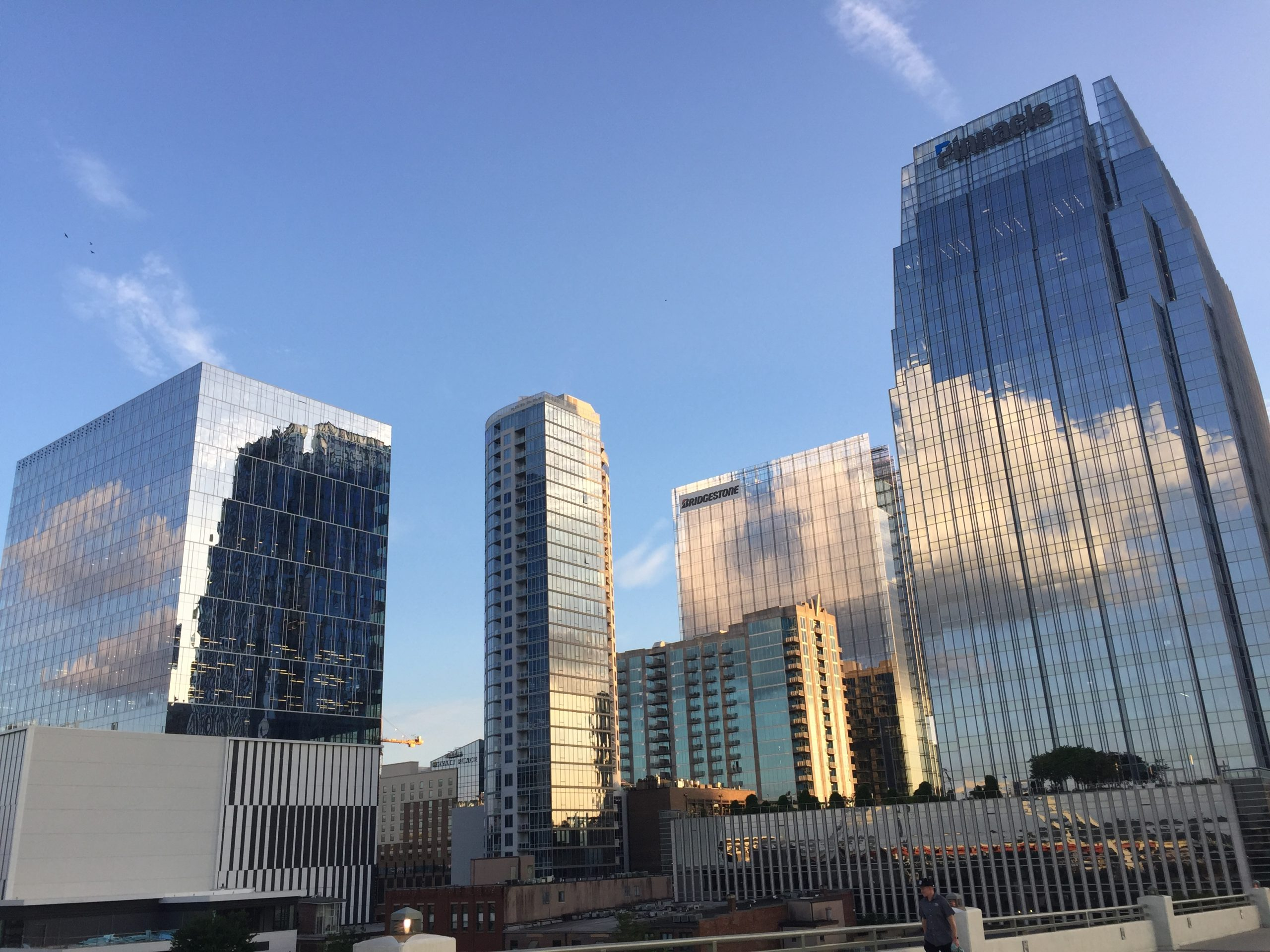 blue sky with buildings reflecting clouds